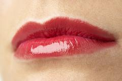 Extreme Close-Up Of Young Woman Wearing Red Lipstick - stock photo
