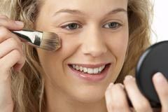 Young Woman Applying Make-Up - stock photo