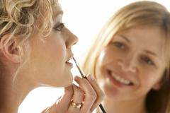 Young Woman Having Her Lipstick Applied - stock photo