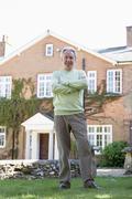 Senior Man Standing Outside House - stock photo