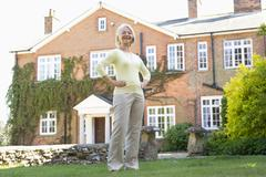 Senior Woman Standing Outside House - stock photo