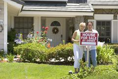 Couple Standing Outside House With Real Estate Sign - stock photo