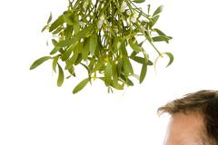 Man Waiting Under Bunch Of Mistletoe Against White Background - stock photo