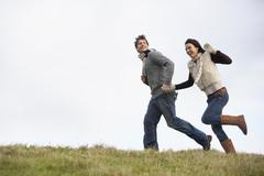 Couple Holding Hands And Running In The Park Stock Photos