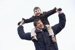Stock Photo of Father Carrying Son On His Shoulders