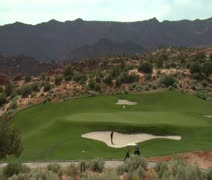 wide shot of golfer hitting ball from sand trap to green - stock footage