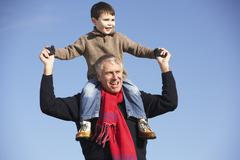 Grandfather Carrying Grandson On His Shoulders Stock Photos