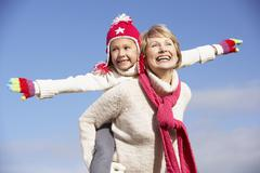 Grandmother Giving Her Granddaughter A Piggy Back Ride Stock Photos