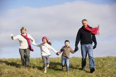 Grandparents And Grandchildren Running In The Park - stock photo