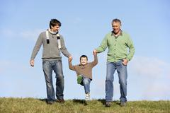 Father And Grandfather Swinging Young Boy - stock photo