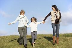 Grandmother And Mother Holding Hands With Young Girl - stock photo