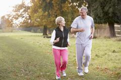 Senior Couple Power Walking In The Park Stock Photos