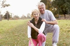 Portrait Of Senior Couple Crouching In The Park Stock Photos
