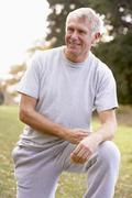 Portrait Of Senior Man Kneeling In Park - stock photo