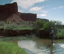 Fly fisherman in stream with red rock cliffs Stock Footage