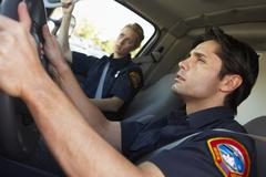 Ambulance driver and colleague on the way to an emergency Stock Photos