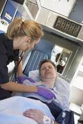 Paramedic attending to patient in ambulance - stock photo