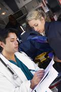 Paramedic advising doctor about arriving patient - stock photo