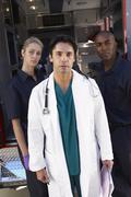 Stock Photo of Portrait of doctor with two paramedics in front of ambulance