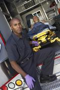 Male paramedic preparing to unload patient from ambulance Stock Photos