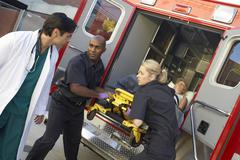 Paramedics and doctor unloading patient from ambulance Stock Photos