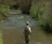 Slow motion pull out shot of fly fisherman and red rock cliffs Stock Footage