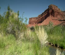 Jib shot of fly fisherman and red rock cliffs Stock Footage