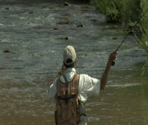 Slow motion tight shot of fly fisherman and red rock cliffs Stock Footage