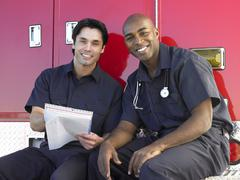 Stock Photo of Two paramedics cheerfully doing paperwork, sitting by their ambulance