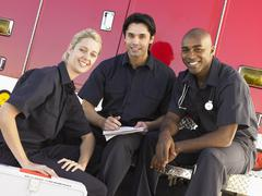 Three paramedics chatting and doing paperwork, sitting by their ambulance Stock Photos