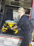 Paramedic removing empty gurney from ambulance - stock photo