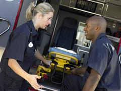 Two paramedics cheerfully removing empty gurney from ambulance Stock Photos
