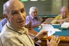 Senior adults playing bridge - stock photo