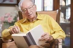 Senior man reading book - stock photo