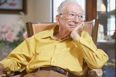 Senior man relaxing in armchair - stock photo