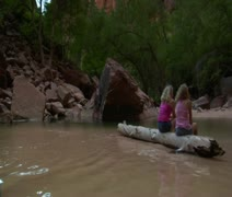 Two girls on a log in shallow water, redrock near - stock footage
