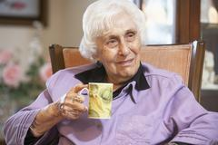 Senior woman drinking hot beverage - stock photo