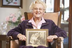 Senior woman holding an old wedding photo Stock Photos
