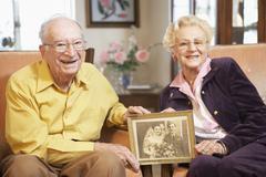 Senior couple holding wedding photo - stock photo