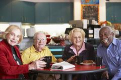 Senior adults having morning tea together - stock photo