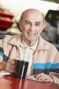 Senior man drinking hot beverage - stock photo