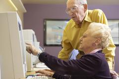 Senior man helping senior woman to use computer - stock photo