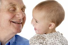 Portrait of grandfather and granddaughter, smiling at each other - stock photo