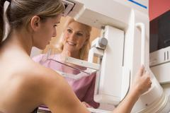 Nurse assisting patient undergoing mammogram Stock Photos