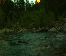Backpacker sits on rock in creek, moutains near - stock footage