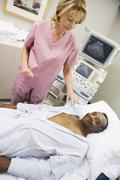nurse checking on patient lying on hospital bed - stock photo
