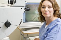 Portrait Of A Nurse Next To An Eye Exam Machine - stock photo