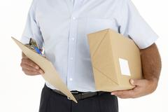 Courier Holding A Parcel And Clipboard Stock Photos