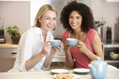 Female Friends Enjoying Tea And Cookies At Home Stock Photos