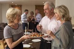 Woman Serving Hors D'oeuvres To Her Guests At A Dinner Party - stock photo